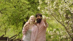Spring couple in blooming garden. Earth day. Green grass field landscape. Farmer man with farmer woman in village on. Farm. Eco farm - eco living stock footage