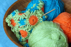 Spring crochet. Cute crochet project with three bright and colourful balls of yarn (green, blue, orange) and crochet hook Stock Photo