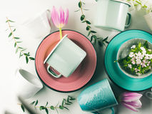 Spring crockery concept with tulips flowers pastel color. Spring tableware crockery concept with tulips flowers pastel color white background. Textured ceramic Stock Image