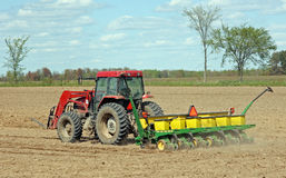 Spring crop planting. Farm tractor and seeder planting crops on a field Stock Images