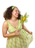 Spring curtsy with a flower. Beautiful young woman doing a playful curtsy while holding a spring flower Royalty Free Stock Image