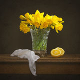 Spring Daffodil Flowers. Bunch of spring daffodils with cut lemons still life on rustic table Royalty Free Stock Photography