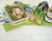 Spring decorative composition. Flowers in a basket and pots of hyacinth, muscari, narcissus. Wooden background. Cozy decor of the Easter. Easter eggs. Colors Stock Photo
