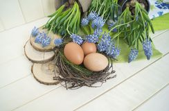 Spring decorative composition. Flowers in a basket and pots of hyacinth, muscari, narcissus. Wooden background. Cozy decor of the Easter. Easter eggs. Colors Royalty Free Stock Photo