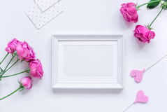 Spring design with peony flower and frame white background top view mock-up. Spring design with peony flower bouquet and frame for mother`s day on white desk royalty free stock image