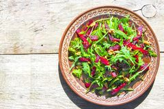 Spring detox salad salad with arugula and boiled beets with walnut kernel and roasted sesame seeds, poured with olive oil in a. Rustic ceramic plate on a wooden royalty free stock image