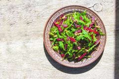 Spring detox salad salad with arugula and boiled beets with walnut kernel and roasted sesame seeds, poured with olive oil in a. Rustic ceramic plate on a wooden royalty free stock photos