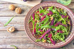 Spring detox salad salad with arugula and boiled beets with walnut kernel and roasted sesame seeds, poured with olive oil in a. Rustic ceramic plate on a wooden royalty free stock images
