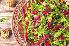 Spring detox salad salad with arugula and boiled beets with walnut kernel and roasted sesame seeds, poured with olive oil in a. Rustic ceramic plate on a wooden royalty free stock photo