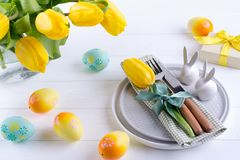 Spring Easter background for menu. Easter egg decoration, bunny, linen napkin on plate and kitchen cutlery on white table royalty free stock images