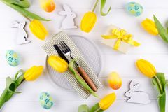 Spring Easter background for menu. Easter egg decoration, bunny, linen napkin on plate and kitchen cutlery on white wooden table stock image