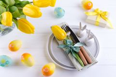 Spring Easter background for menu. Easter egg decoration, bunny, linen napkin on plate and kitchen cutlery on white wooden table stock photos