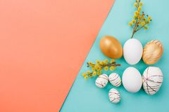 Spring Easter composition on colorful background. Decorative Easter eggs and pussy willow twigs on two-colored paper background with copy space Stock Image