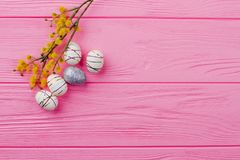 Spring Easter composition and copy space. Pussy willow twig and decorative Easter eggs on colorful wood, space for text. Creative Easter crafts. Minimal Easter Stock Images