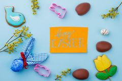 Spring Easter composition and greeting card. Easter chocolate eggs, cookies, molds and pussy willow on blue background. Happy Easter holidays Royalty Free Stock Images