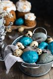 Spring easter concept, - naturally dyed easter eggs, quail eggs, feathers, easter cake, dark wooden background, copy space. Spring organic easter concept stock photo