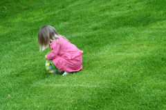 Spring Easter Egg Hunt. Young toddler finding Easter eggs on lawn Royalty Free Stock Photos