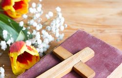 Spring easter flowers and cross on wooden background royalty free stock photos