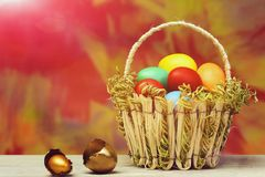 Spring easter holiday, colorful eggs and golden egg in basket. Happy easter egg. holiday bunny and eggs, spring flower backround straw basket with easter painted Royalty Free Stock Photography