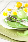 Spring or easter table setting with jonquil. Easter or spring white dinner table setting with fresh daffodil flowers and pastel green decorations. Chic plates stock image