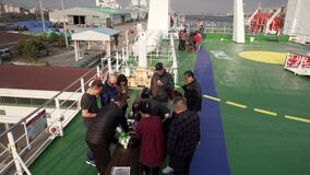 Passengers of an Asian-looking ferry have a picnic on the upper deck of the liner.