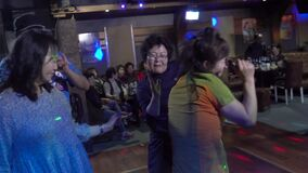 Passengers of the liner dance at an evening disco in the sea bar.