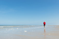 Spring för äldre man på stranden Royaltyfri Foto