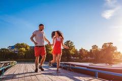 Spring för den unga mannen och kvinnalängs sommarfloden ansluter Par som har gyckel på solnedgången Koppla av för grabbar arkivbilder