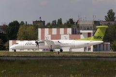 Spring för flygplan för AirBaltic De Havilland Kanada DHC-8-402Q streck 8 på landningsbanan Arkivbilder