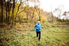 Spring för hög man i natur med den smarta telefonen och hörlurar Fotografering för Bildbyråer