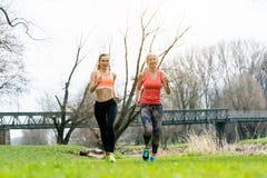 Spring för hög och ung kvinna som sport på en äng Arkivbilder