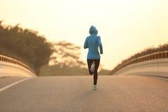Spring för idrottsman nen för konditionkvinnalöpare på soluppgångvägen fotografering för bildbyråer