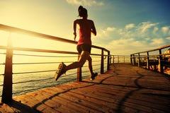 Spring för konditionkvinnalöpare på sjösidastrandpromenaden Royaltyfri Foto