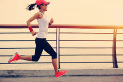 Spring för kvinnalöpareidrottsman nen på sjösidavägen royaltyfri bild