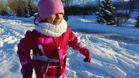 Spring för lilla flickan för sidosikten i vinter parkerar Solig vinterdag lager videofilmer