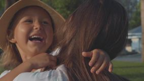 Spring för litet barn in i hennes kramar för moder` s på parkera i ultrarapid arkivfilmer
