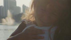 Spring för litet barn in i hennes kramar för moder` s på parkera i ultrarapid stock video