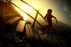 Spring för slinga för konditionkvinnalöpare på sjösidabergtrappa Royaltyfri Bild