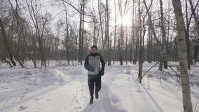 Spring för ståendeidrottsman nenman i vinterskogslut upp Vintern som joggar i stad, parkerar royaltyfri foto