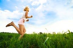 Spring för ung dam på en lantlig väg under solnedgång Royaltyfri Foto