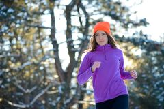 Spring för ung kvinna i härlig vinterskog på Sunny Frosty Day Aktivt livsstilbegrepp arkivfoto