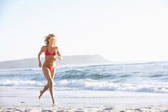 Spring för ung kvinna längs den Sandy Beach On Holiday Wearing bikinin Royaltyfria Foton