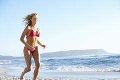 Spring för ung kvinna längs den Sandy Beach On Holiday Wearing bikinin Arkivfoto