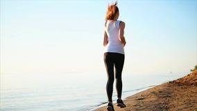 Spring för ung kvinna på sandstranden nära havssikten från baksidan arkivfilmer