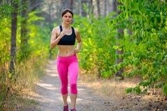 Spring för ung kvinna på slingan i den härliga lösa Forest Active Lifestyle Concept Utrymme för text arkivbilder
