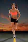 Spring för ung kvinna på solnedgången Royaltyfri Foto