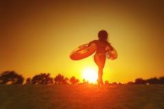 Spring för ung kvinna på solnedgången på stranden Royaltyfri Fotografi
