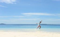 Spring för ung man i grunt vatten på den tropiska stranden Arkivbild