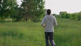 Spring för ung man i parkera på spåret Sport och sund livsstil arkivfilmer