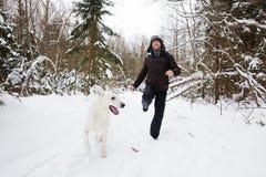 Spring för ung man i skogen med den vita hunden royaltyfri foto